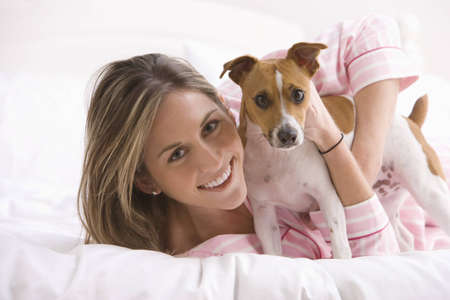 An attractive young woman wearing pink pajamas is holding a dog while laying on a bed. Horizontal shot. Stock Photo - 7466746