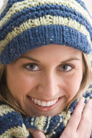 An attractive young woman is smiling and wearing a blue and beige knit cap and scarf. Vertical shot. Stock Photo