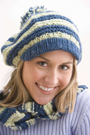 An attractive young woman is smiling and wearing a blue and beige knit cap and scarf. Vertical shot. photo