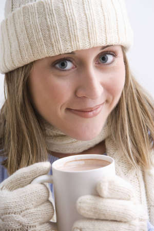 An attractive young woman is smiling and wearing a knit cap, gloves and holding a cup of hot cocoa. Vertical shot.