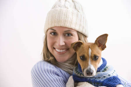 An attractive young woman wearing a knit cap and holding her terrier. Both are wearing sweaters. Horizontal shot. photo