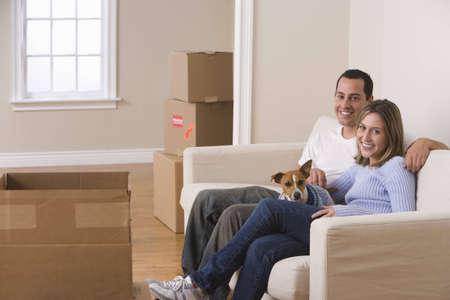 Ein junges Paar und Ihren Hund sitzen auf einem Sofa im Wohnzimmer. Bewegenden Boxes sind auf dem Boden um Sie herum angeordnet. Horizontale erschossen.