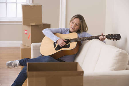 An attractive young woman is sitting on a couch and playing the guitar. Moving boxes can be seen in the background. Horizontal shot.