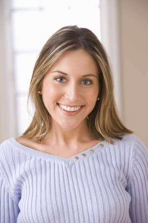Portrait of an attractive young woman smiling and wearing a sweater. Vertical shot. photo