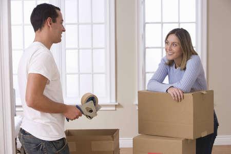 Ein attraktives junges Paar ist in den Prozess der Verpackung f�r ein bewegen. Horizontale erschossen.