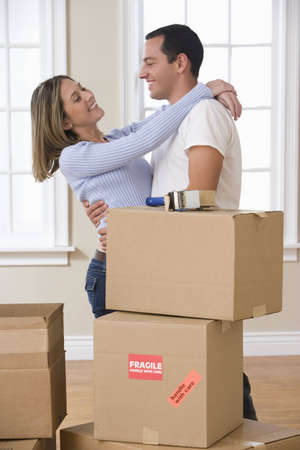An attractive young couple is hugging while in the process of packing for a move. Vertical shot. photo