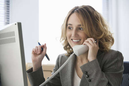 A young businesswoman is smiling at she talks on the telephone and looks at her computer screen.  Horizontal shot.