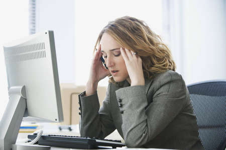 Eine junge frau gesch�ftsfrau sucht betonten, wie Sie an Ihrem Computer arbeitet.  Horizontale erschossen.
