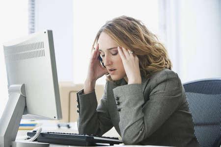 estr�s: Una joven empresaria est� buscando estresada como ella trabaja en su equipo. Horizontal a tiros.