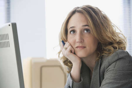 A young businesswoman slouches at her desk with a bored expression on her face.  Horizontal shot.