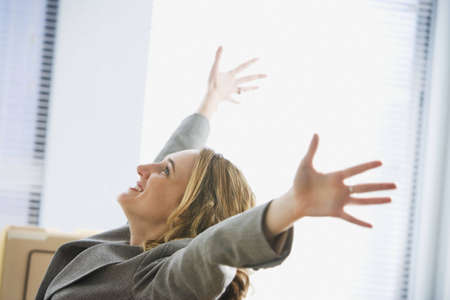 A young businesswoman is sitting in an office with her hands outstretched in the air. Horizontal shot. Stock Photo
