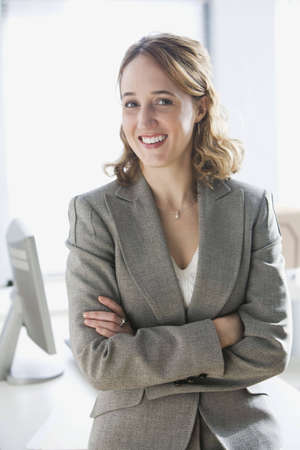 A young businesswoman is sitting on an office desk and smiling at the camera.  Vertical shot. Stock Photo
