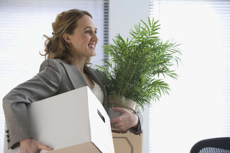 office desk: A young businesswoman smiles as she carries her office belongings in her hands.  Horizontal shot.