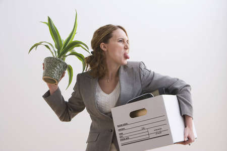 belongings: Young businesswoman sticks out her tongue while holding a plant and other office belongings. Horizontal shot. Stock Photo