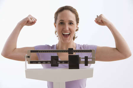 A young woman flexes her arms while standing on a scale and smiling at the camera. Horizontal shot. Isolated on white. Stock Photo