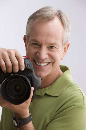 A man is holding a camera as he gets ready to take a photograph. Vertical shot.
