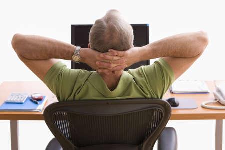 R�ckansicht eines Mannes, die am Schreibtisch an einen Laptop sitzen. Er ist zur�ck in seinem Stuhl mit den H�nden hinter dem Kopf sitzen. Horizontale erschossen.