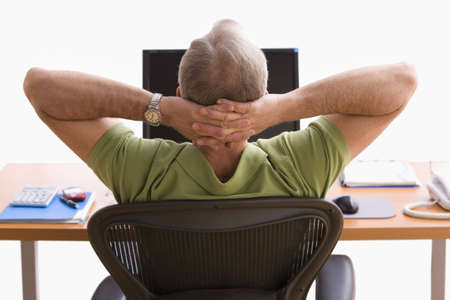 hands behind head: Rear view of a man seated at a desk in front of a laptop. He is sitting back in his chair with his hands behind his head. Horizontal shot.