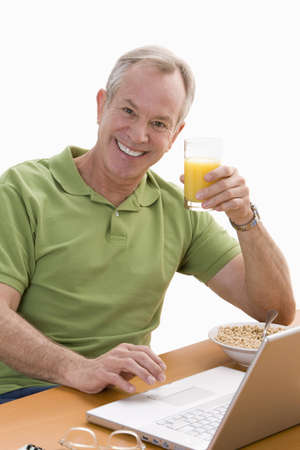 A man is seated at a desk in front of a laptop.  He is eating breakfast and smiling at the camera.  Vertical shot. photo