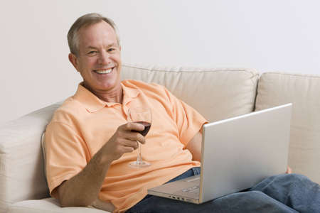 A man is lying on the couch with his laptop and a glass of wine.  He is smiling at the camera.  Horizontal shot. Stock Photo