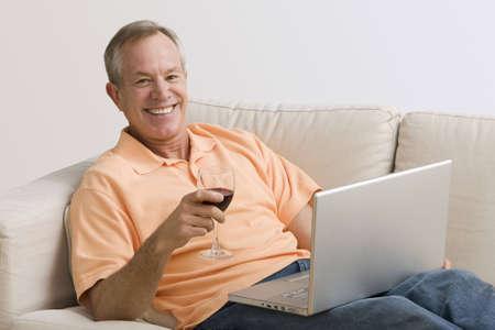 Ein Mann ist mit seinen Laptop und einem Glas Wein auf der Couch liegen.  Er l�chelt in die Kamera.  Horizontal gedreht.
