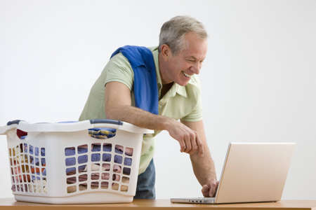 A man is working on a laptop while he folds laundry.  He is smiling and looking away from the camera.  Horizontal shot.