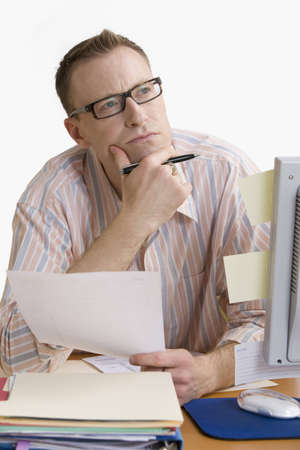 A man doing work at a computer desk, deep in thought.  Vertical shot.  Isolated on white.