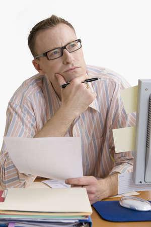Ein Mann, die Arbeit am Computerschreibtisch, tief in Gedanken. Vertikal gedreht. Isolated on White.