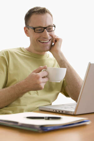 A man is seated at a computer desk and is working on a laptop.  He is enjoying a cup of coffee.  Vertical shot.  Isolated on white.