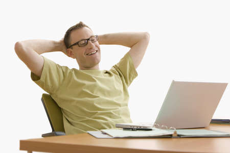 Man leans back in his chair while working on his laptop at home.  Horizontal shot.  Isolated on white.