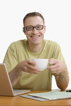 Man with a cellphone ear piece and sitting at his desk enjoys a cup of coffee while smiling for the camera.  Vertical shot.  Isolated on white.