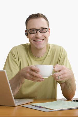 Mann mit einem Handy Ohr St�ck und an seinem Schreibtisch sitzen genie�t eine Tasse Kaffee w�hrend l�chelnd f�r die Kamera.  Vertikal gedreht.  Isolated on White. Lizenzfreie Bilder