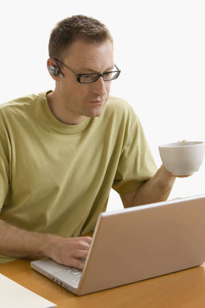 A man is seated at a computer desk and is working on a laptop.  He is holding a cup of coffee in one hand.  Vertical shot.  Isolated on white.