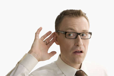 job loss: A businessman has his hand by his ear to gesture that he cant hear.  Horizontal shot.  Isolated on white.