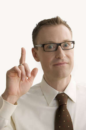 A businessman gestures with his finger that he has come up with an idea.  Vertical shot.  Isolated on white.