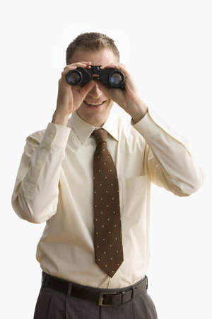 A businessman is looking at the camera through binoculars and smiling.  Vertical shot.  Isolated on white.