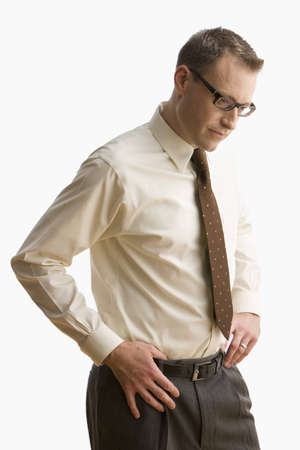 Businessman looks down at the ground with his hands on his hips.  Vertical shot.  Isolated on white. Stock Photo
