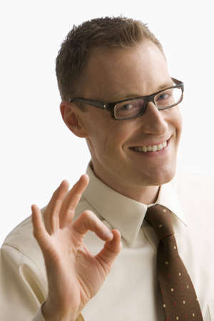 A businessman gestures an okay signal with his hands and smiles at the camera.  Vertical shot.  Isolated on white.