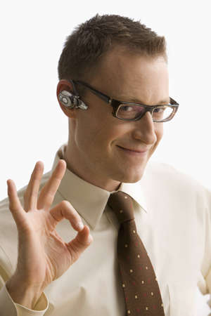 A businessman with a cellphone ear piece gestures an okay signal with his hands and smiles at the camera.  Vertical shot.  Isolated on white. Stock Photo