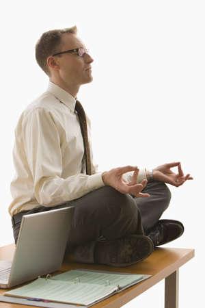 Ein Gesch�ftsmann ist auf seinem Schreibtisch neben seinem Laptop zu meditieren.  Vertikal gedreht.  Isolated on White.
