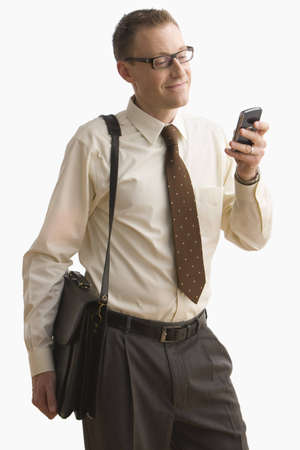 Businessman smiles as he writes a text message on his cellphone.  Vertical shot.  Isolated on white. Stock Photo