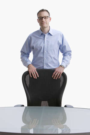 Businessman stands with his hands on a conference room chair.  Vertical shot.  Isolated on white.