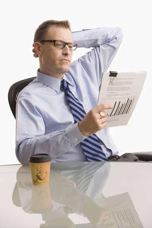 Ein Gesch�ftsmann sitzt an einem Schreibtisch und schaut Papierkram mit einem schweren Ausdruck auf seinem Gesicht.  Vertikal gedreht.  Isolated on White. Lizenzfreie Bilder