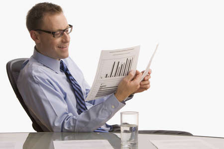 A businessman is seated at a desk and is looking at paperwork with a happy expression on his face.  Horizontal shot.  Isolated on white.