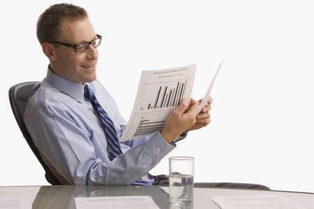 Ein Gesch�ftsmann sitzt am Schreibtisch und schaut Papierkram mit einem happy Ausdruck auf seinem Gesicht.  Horizontal gedreht.  Isolated on White. Lizenzfreie Bilder
