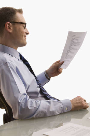 A businessman is seated at a desk and is looking at paperwork with a happy expression on his face.  Vertical shot.  Isolated on white.