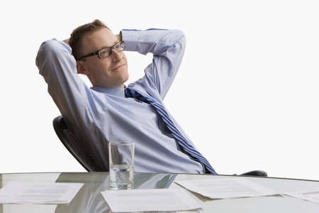 A businessman reclines back in his chair at work with paperwork spread across his table.  Horizontal shot.  Isolated on white.
