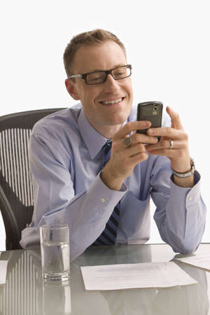 A businessman is seated at a desk in an office and is texting on a cell phone.  Vertical shot.  Isolated on white. Stock Photo