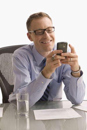 Ein Gesch�ftsmann sitzt an einem Schreibtisch in einem B�ro und ist auf einem Handy Texting.  Vertikal gedreht.  Isolated on White.