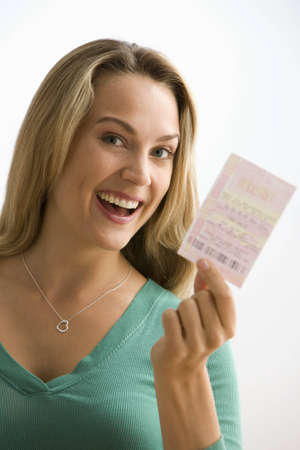 A young woman is holding up a lottery ticket and smiling at the camera.  Vertical shot.   Stock Photo